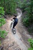 Woman mountain biker / s-curve. A woman mountain biker on a trail zooms down an s-curve path Stock Photos