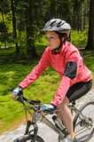 Woman mountain biking in forest motion blur Royalty Free Stock Photo