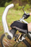 Woman mountain biking and holding handlebars Royalty Free Stock Photos