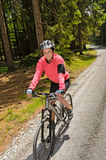 Woman mountain biking in sunny forest smiling. Woman mountain biking in sunny forest cycling path smiling Royalty Free Stock Photography