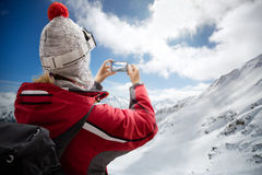 Woman on mountain making photo with smartphone Stock Photos
