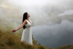 Woman in mountain mystical air. Young woman in long white dress breathing fresh mountain air Royalty Free Stock Photo