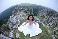 Woman on mountain peak. Round Earth perspective of woman in white dress sitting on mountain Royalty Free Stock Photos
