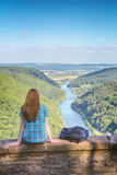 Woman and Mountain River Scenery. A young female hiker rests at a vantage point overseeing the river Saar at Saarschleife in Germany. Summer view with a blue sky Stock Photography