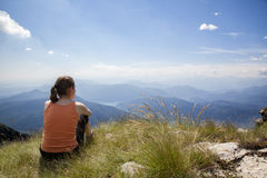 Woman on mountain top. Woman sitting on mountain top of Monte Generoso admiring mountain landscape around Lugano lake and blue sky Royalty Free Stock Photos