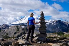 Woman on mountain top with stone cairn against snow capped Mount Baker. Stock Photos