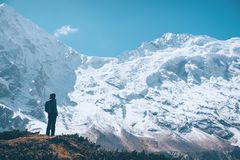 Woman on the mountain trail and looking on snow covered rocks Stock Images