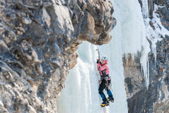 Woman mountaineer climbs on vertical icefall Royalty Free Stock Photo