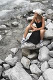 Woman in mountains. Model with photo camera and backpack on mountain river Stock Photo