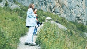 A woman in the mountains looks at a beautiful landscape. Girlfriends on a mountain hike in Altai stock footage