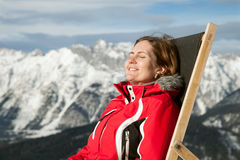 Woman at mountains sits on sun-lounger Royalty Free Stock Photo
