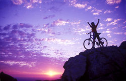 Woman on a mountaintop with bike Royalty Free Stock Image