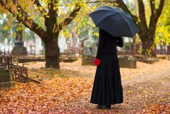 Woman Mourning at Cemetery. Woman in Mourning at Cemetery in Fall, with Black Umbrella Stock Photos