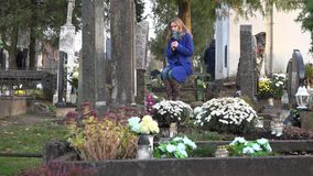 Woman mourning near marble tombstone in cemetery in autumn. 4K stock video footage