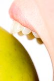 Woman mouth biting yellow apple. Close up of woman mouth biting a delicious fresh yellow apple, isolated on white background Royalty Free Stock Photos