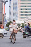 Woman with mouth cap cycles in busy traffic, Kunmin, China Royalty Free Stock Photo