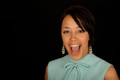 Woman with mouth open. Woman smiling and yelling with her mouth open.  Isolated against a black background Royalty Free Stock Photo