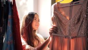 Woman moves apart hangers on rack choosing dress inside room stock video footage