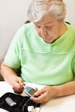 Woman moves test strip into the glucose meter Stock Photos