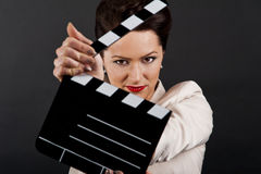 Woman with movie clap. Over black background Stock Photography