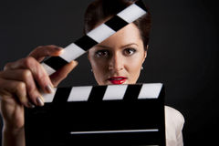 Woman with movie clap close up Stock Photos