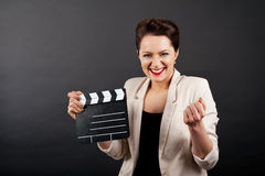 Woman with movie clap over black background Royalty Free Stock Image
