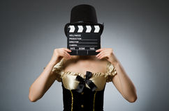 Woman with movie clapboard. Against grey background Royalty Free Stock Photos