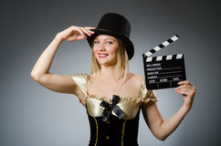 Woman with movie clapboard. Against grey background Royalty Free Stock Photo