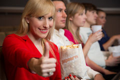 Woman in movie theatre showing thumbs up Stock Image
