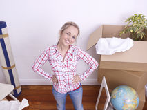Woman moving in. Young woman opening boxes after moving house Royalty Free Stock Image