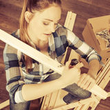 Woman moving into apartment assembly furniture. Stock Photography