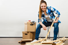 Woman moving into apartment assembly furniture. Royalty Free Stock Image