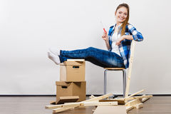 Woman moving into apartment assembly furniture. Royalty Free Stock Images
