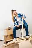 Woman moving into apartment assembly furniture. Royalty Free Stock Photography