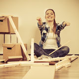 Woman moving into apartment assembly furniture. Royalty Free Stock Photos