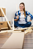 Woman moving into apartment assembly furniture. Stock Image