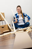 Woman moving into apartment assembly furniture. Stock Photos