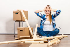 Woman moving into apartment assembly furniture. Worried confused woman moving into new apartment house assembling furniture. Young girl arranging interior and Stock Images