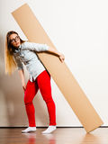 Woman moving into apartment carrying heavy box. Woman moving into new apartment house carrying heavy carton box with furniture. Young girl arranging interior Royalty Free Stock Images