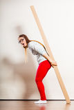 Woman moving into apartment carrying heavy box. Royalty Free Stock Images