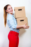 Woman moving into apartment house carrying boxes. Royalty Free Stock Images