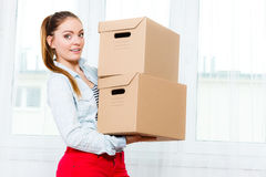 Woman moving into apartment house carrying boxes. Royalty Free Stock Image