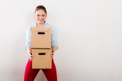 Woman moving into apartment house carrying boxes. Royalty Free Stock Photo