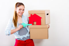 Woman moving in with boxes and paper house key. Happy woman moving in carrying cartons boxes with red paper house and key. Young girl arranging interior and Royalty Free Stock Image