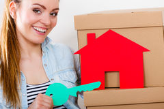 Woman moving in with boxes and paper house key. Happy woman moving in carrying cartons boxes with red paper house and key. Young girl arranging interior and Stock Image