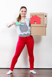 Woman moving in with boxes and paper house key. Happy woman moving in carrying cartons boxes with red paper house and key. Young girl arranging interior and Royalty Free Stock Photography
