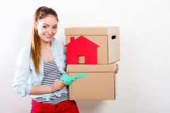 Woman moving in with boxes and paper house key. Happy woman moving in carrying cartons boxes with red paper house and key. Young girl arranging interior and Stock Images