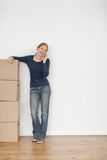 Woman with Moving Boxes on the Phone. A happy young woman standing in an empty room with moving boxes and having a conversation on the phone Stock Image
