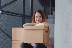Woman with moving boxes sitting on stairs in house. Young redhead woman with moving boxes sitting on stairs in house. European ethnicity Stock Photography