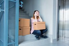 Woman with moving boxes sitting on stairs in house. Young redhead woman with moving boxes sitting on stairs in house. European ethnicity Stock Images